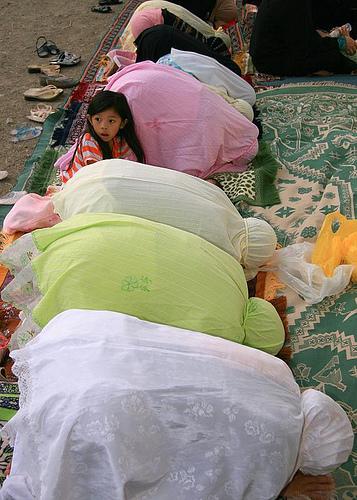 Des femmes prient tête contre le sol. Une petite fille curieuse lève la tête et on lit l'étonnement sur son visage, mais qu'à-t-elle bien pu voir?